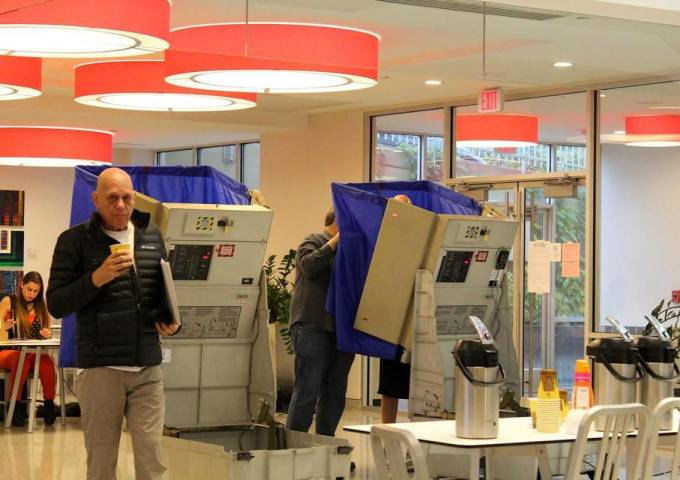 Man holding coffee walking in voting area