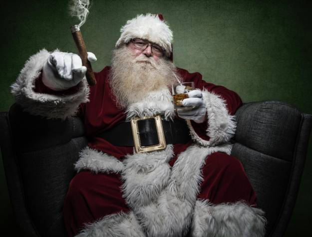 Image of Santa holding a drink and a cigar sitting in a chair