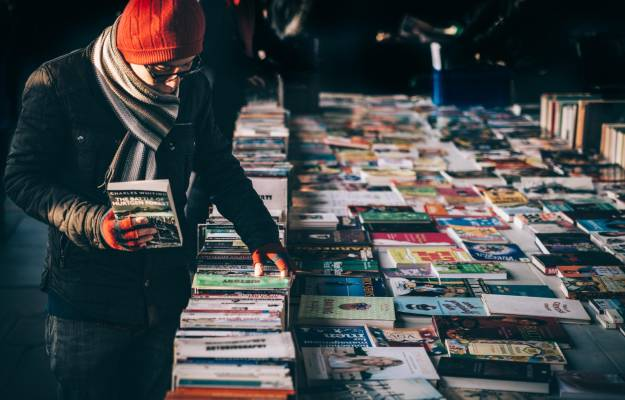 Man looking at books in a flea market