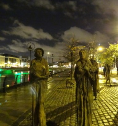 """The Famine"" installation at night along the River Liffey in Dublin"