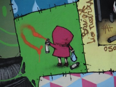 Little Red tagging spray painting the wall in Melbourne