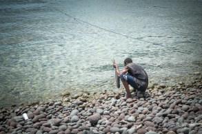 Un pêcheur vide le poisson au bord de la mer