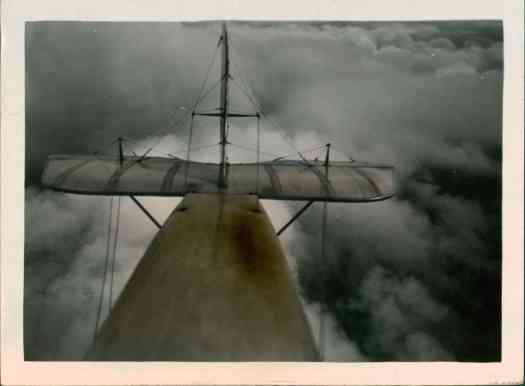 biplane tail above clouds