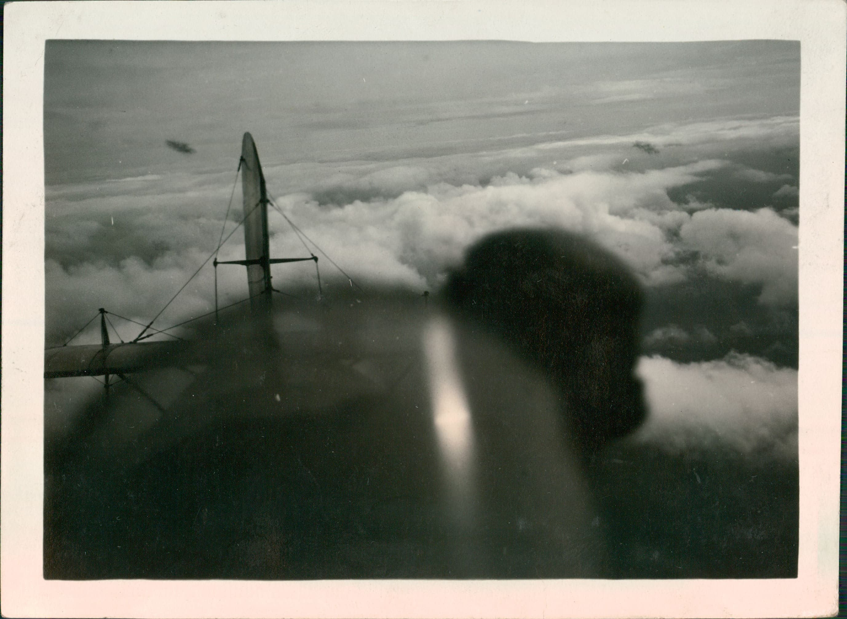 biplane pilot and plane's tail above clouds.