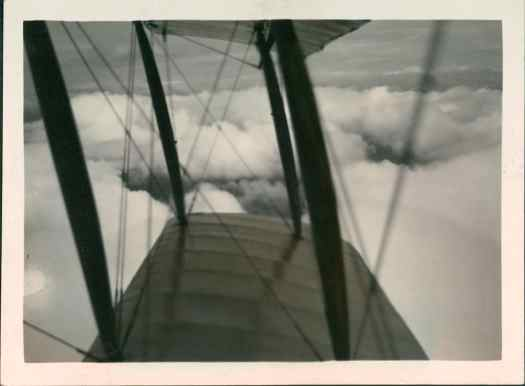 Biplane wing above clouds