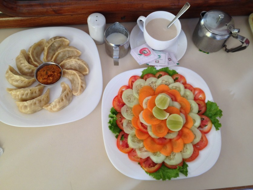"Steamed Chicken Momos, Hot Milk Tea, ""Green"" Salad"