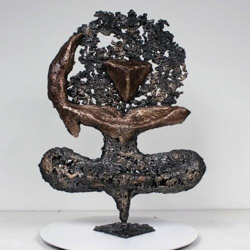 Sculpture représentant  un homme en position de yoga ou de danse en accord avec un symbole calligraphique d'un tableau d'Ikken Koceila. Sculpture en dentelle de Bronze et d'Acier. La dentelle de métal est obtenue en faisant fondre le métal au goutte à goutte dans un moule en sable, ce qui garantit que chaque sculpture est unique. La sculpture est signée et vendue avec un certificat d'authenticité.  Pièce unique Hauteur 36 cm - Largeur 26 cm - Profondeur 7 cm