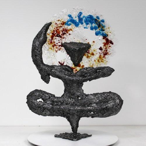 Sculpture représentant un homme en position de yoga ou de danse en accord avec un symbole calligraphique d'un tableau d'Ikken Koceila. Sculpture en verre et en dentelle d'Acier. La dentelle de métal est obtenue en faisant fondre le métal au goutte à goutte dans un moule en sable, ce qui garantit que chaque sculpture est unique. La partie en verre est réalisée en faisant fondre du verre de différentes couleurs coupés en petits morceaux (technique du fusing). La sculpture est signée et vendue avec un certificat d'authenticité.  Pièce unique  Hauteur 36 cm - Largeur 27 cm - Profondeur 8 cm