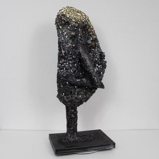 Cette sculpture est réalisée en faisant fondre le métal et en assemblant les gouttes d'acier (les parties noires), de bronze (les parties marrons) et de laiton (les parties dorées). Cette sculpture est fixée sur un socle en gouttes d'acier (21 x 29 x 3 cm) C'est une pièce unique, signée sur le socle et accompagnée de son certificat d'authenticité. Hauteur 69 cm - Largeur 29 cm - Profondeur 21 cm