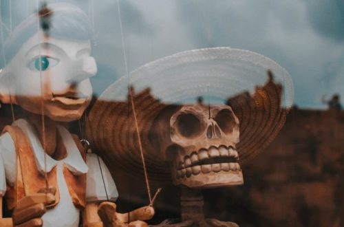 pinocchio dans une vitrine avec une tête de mort à côté
