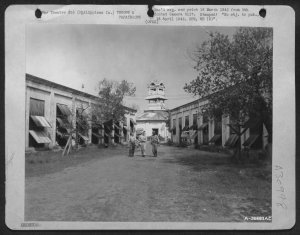 Two just released prisoners walk with G.I. at Old Bilibid Prison, February 1945
