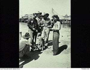"MANILA, THE PHILIPPINES, 1945. FORMER INTERNEES FROM SANTO TOMAS UNIVERSITY INTERNMENT CAMP WITH RAAF PERSONNEL AT NICHOLLS FIELD AIRSTRIP PRIOR TO RETURNING TO AUSTRALIA AFTER LIBERATION. THE CIVILIANS ARE FRANK AND PHYL BUTTFIELD AND THEIR DAUGHTER PAM. RAAF PERSONNEL ARE SERGEANT MATT LACEY (REAR); LEADING AIRCRAFTMAN ""BLUE"" CUTLER (CENTRE) AND LAC E. GWYTHER (SQUATTING). (DONOR: B. COOPER)."