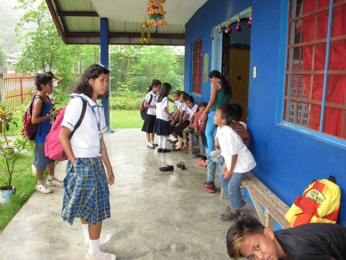 Es regnet und einige Schüler warten nach dem Mittagessen noch vor dem Batulongcenter.