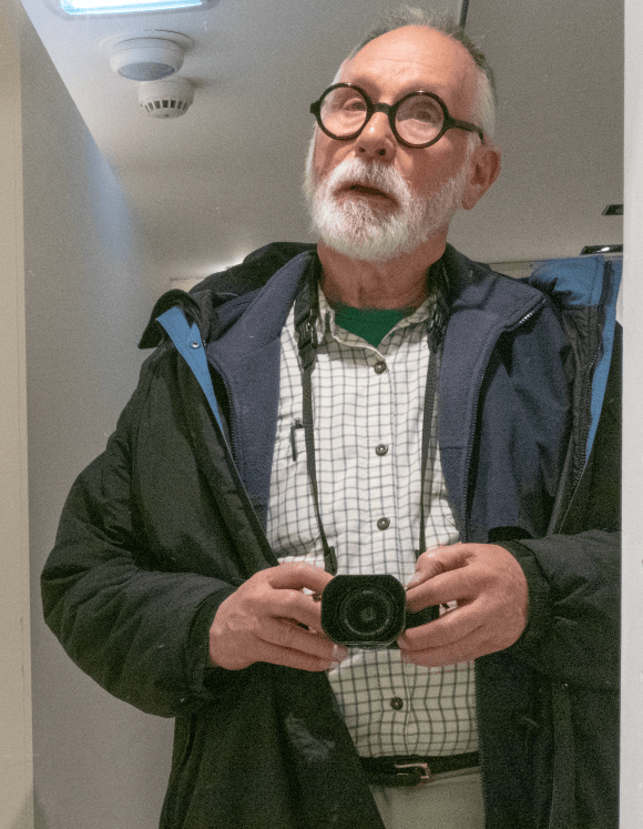 A mirror self-portrait of Phillip Periman. He is wearing cold-weather clothing and round, black glasses. His camera is hanging around his neck as he takes the picture.