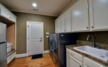 Wonderful laundry room with white cabinets and granite countertops.