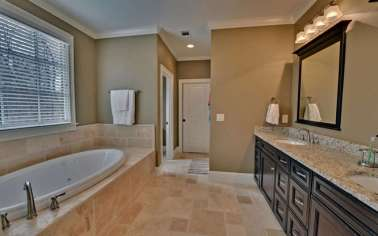 Masterbath with a double vanity and large tub to relax in.
