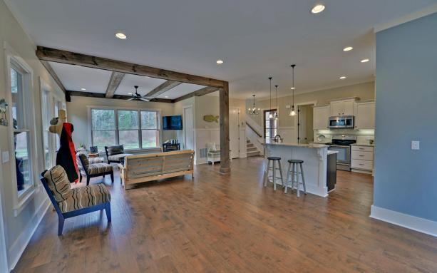 Great room with beams and hardwood floors in an open concept.