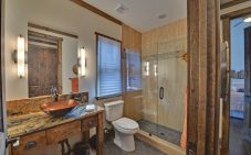 Guest bath with a tiled shower behind glass doors and a standing vanity featuring a granite top and raised bowl.
