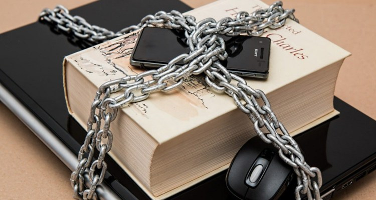 Laptop smartphone ane book chained together