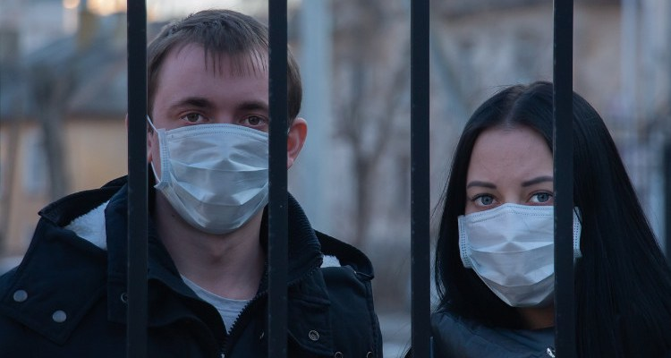 Two people with masks behind bars