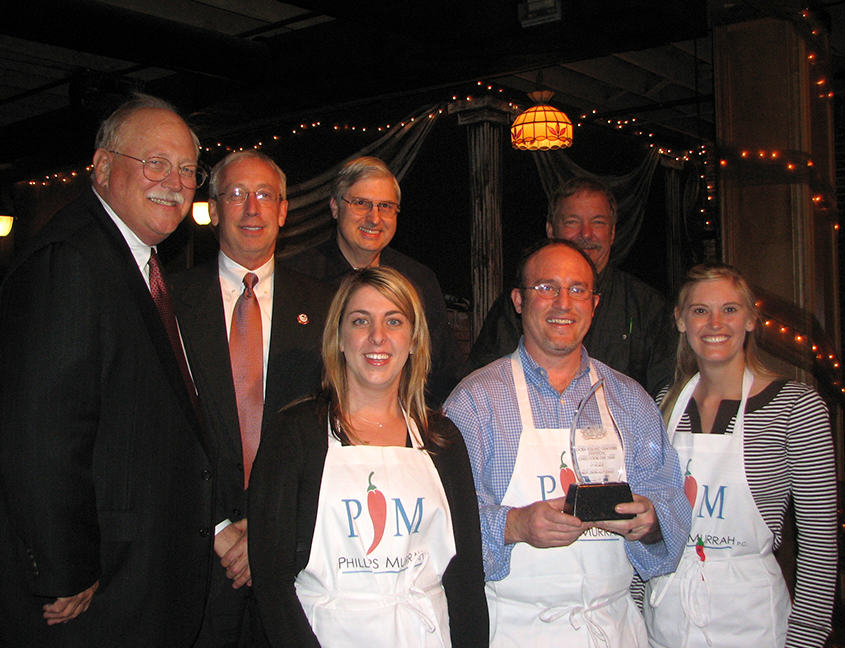 Directors Dawn Rahme, Juston Givens, and Jennifer Miller stand with Chili Cookoff judges after receiving their trophy.