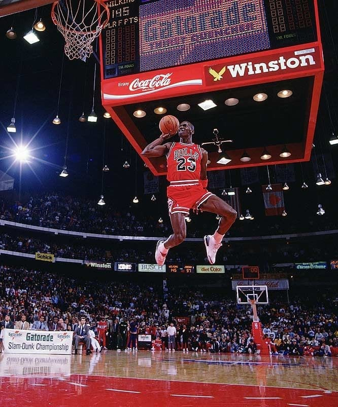 Michael Jordan soaring through the air  with the ball in one hand, behind his head. This is part of the iconic history of the NBA