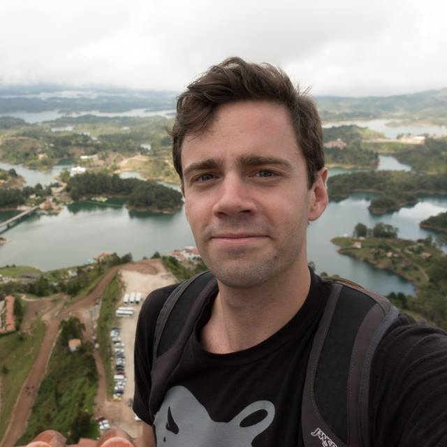A selfie photo of Jono Matusky, a white man with brown hair and a black t-shirt with a landscape in the background.