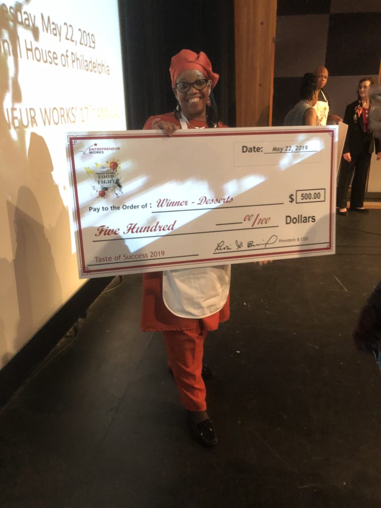 Nefertari Muhammad of Sister's Original Supreme Pies is in the photo wearing her apron and holding a giant check.