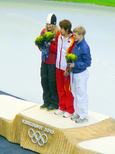 The lady in the middle won the gold. But she was humble enough to invite the other ladies to join her.