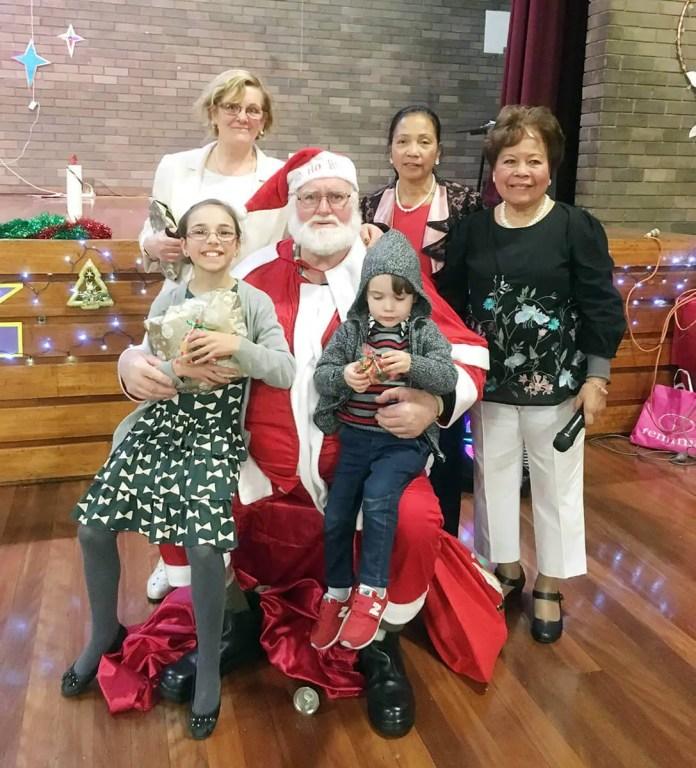 Santa with (standing from L-R) Elizabeth Grillo, President Cora Bojarski and Treasurer Cora Paras.