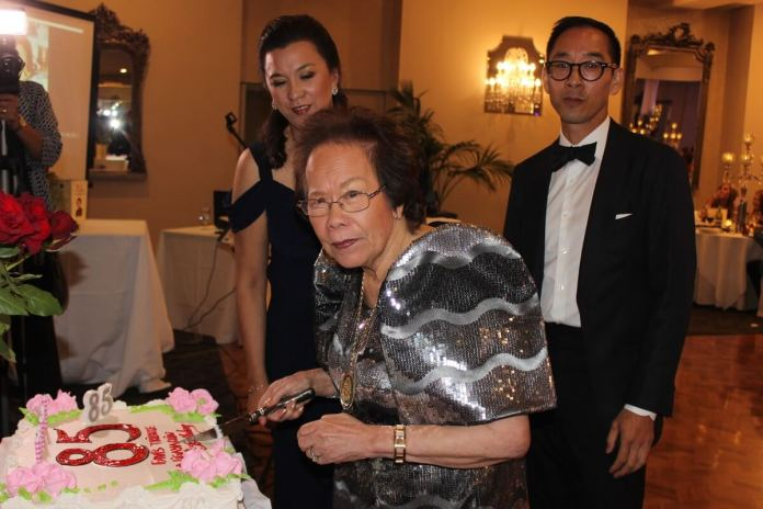 Ligaya Chin cuts her birthday cake. With her are here children, Denise and Terence.