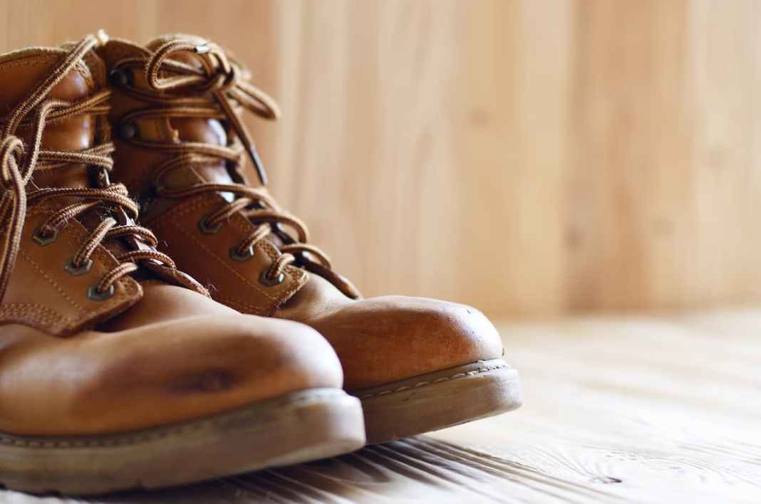 yellow-leather-used-work-boots-on-wooden-background