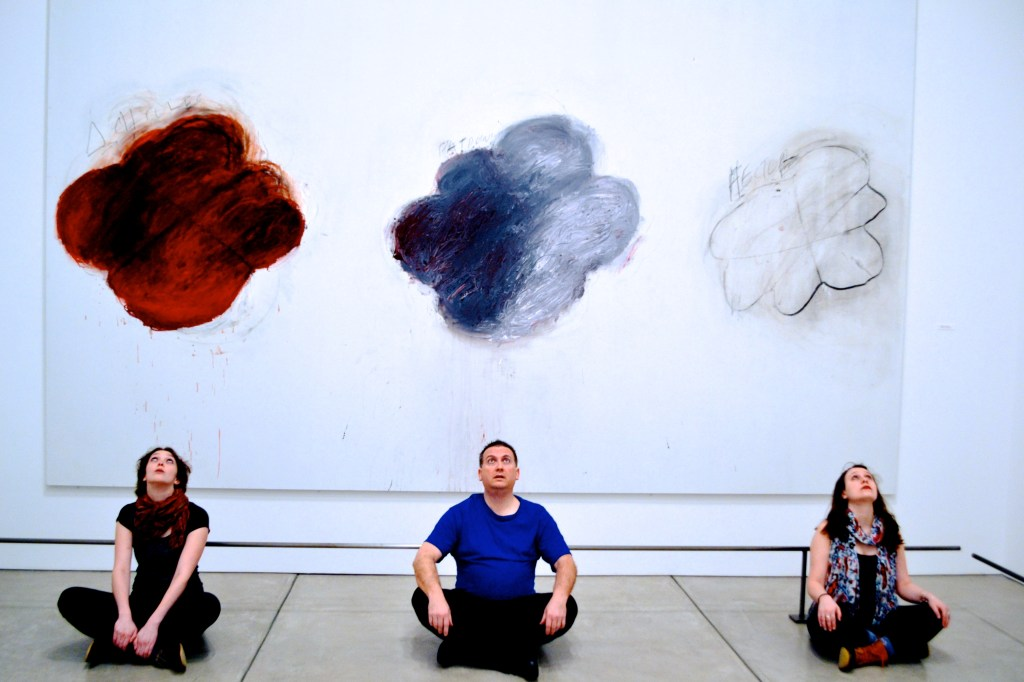 The cast of FIFTY DAYS AT ILIUM in front of the paintings Fifty Days at Iliam. Photo credit: Hannah Van Sciver.