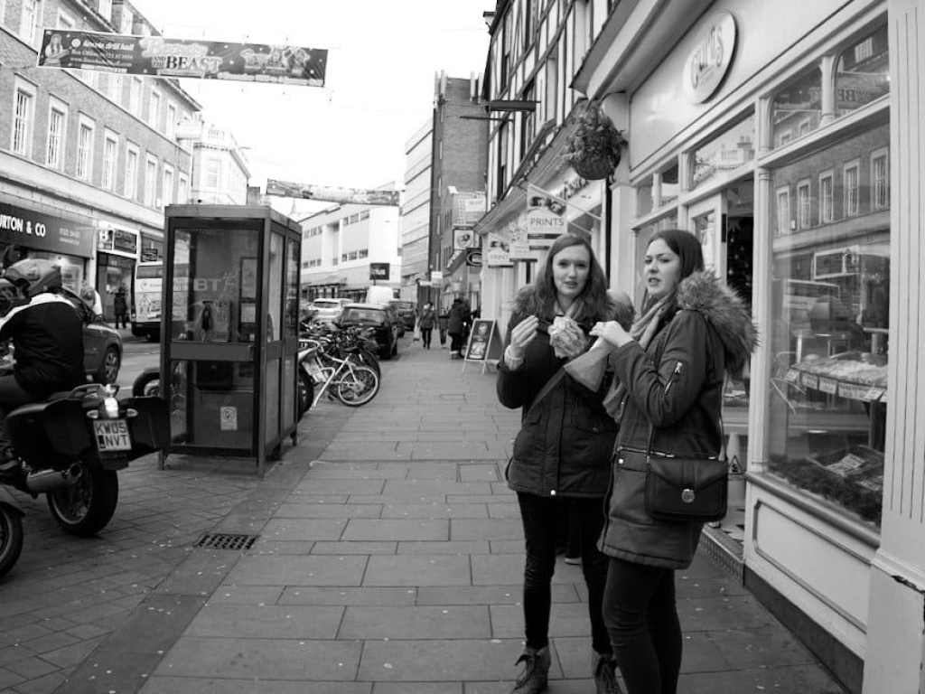 street photograph of 2 women eating outside cake shop