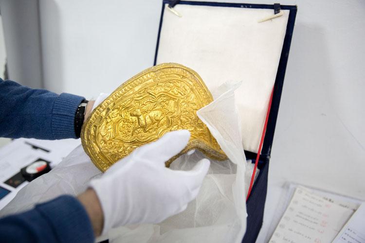 Een onderdeel van het gouden zadel wordt verpakt. Nationaal Militair Museum.