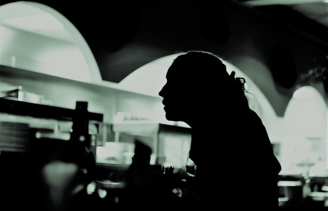 A silhouette of a hospitality worker looking through a service hatch