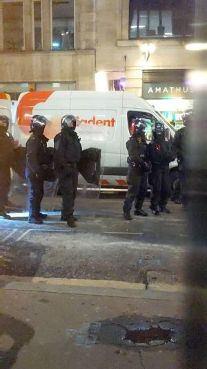 Police in riot gear waiting outside of the squat.