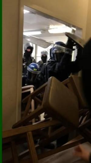 Police in riot gear smash through a barricade of chairs.