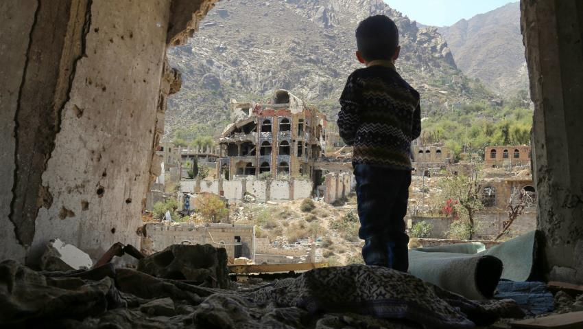 Child in Yemen looking out over rubble