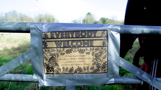 """Sign saying """"Everybody Welcome"""" duct taped over a """"No Trespassing"""" sign on a gate"""