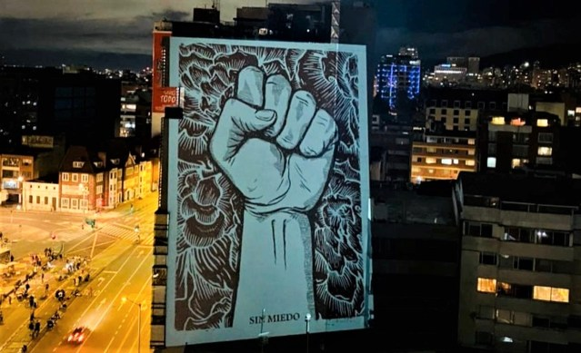 Image of a clenched fist projected onto a tower block in Colombia