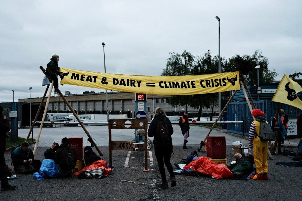 """Protesters outside Heywood McDonald's distribution centre holding a banner that says """"Meat & dairy = climate crisis"""""""