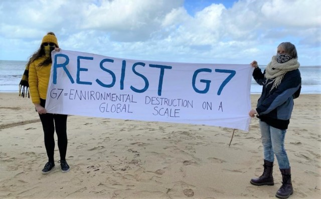 """Two people on a beach holding a banner that says """"Resist G7"""" and """"G7 = Environmental Destruction on a Global Scale"""""""