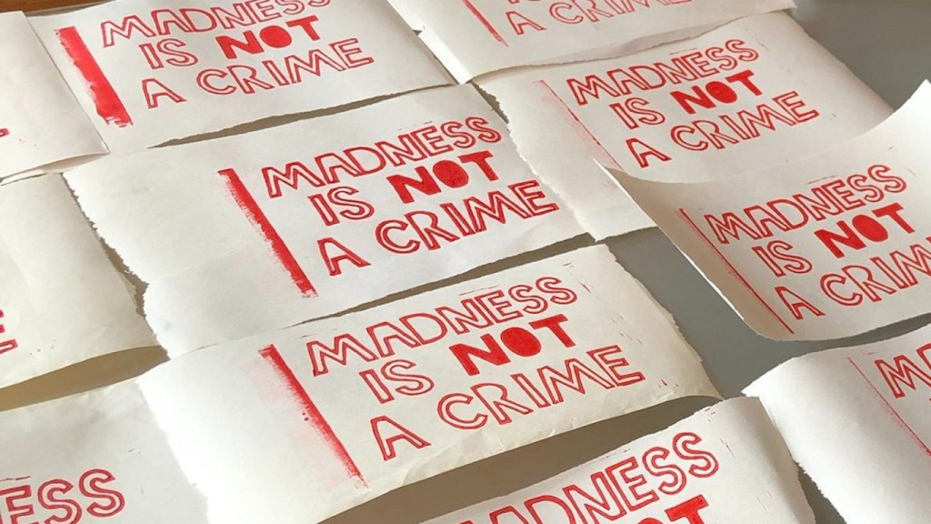 """Several sheets of paper saying """"Madness is not a crime"""" in red lettering"""