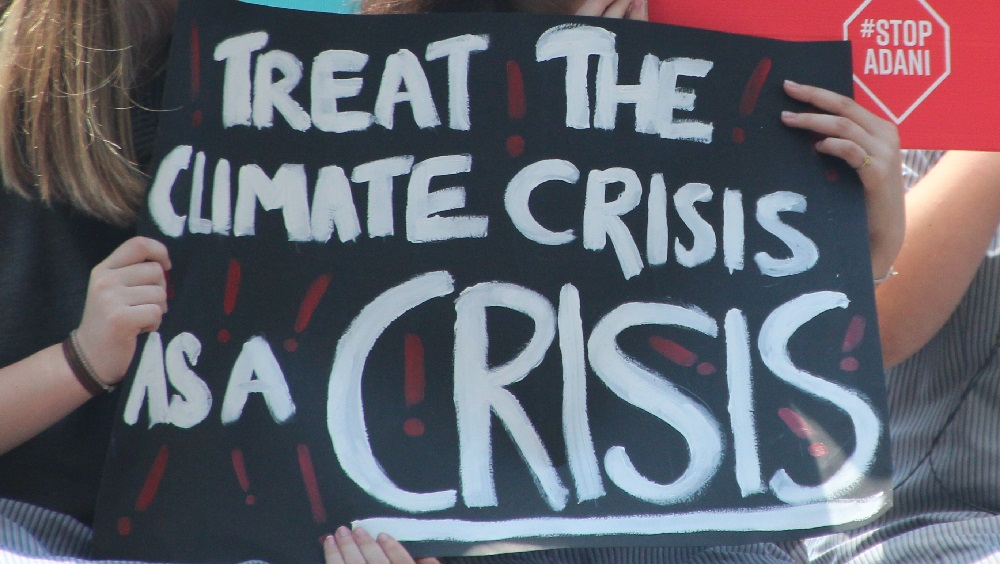 Banner saying 'Treat the Climate Crisis as a crisis'