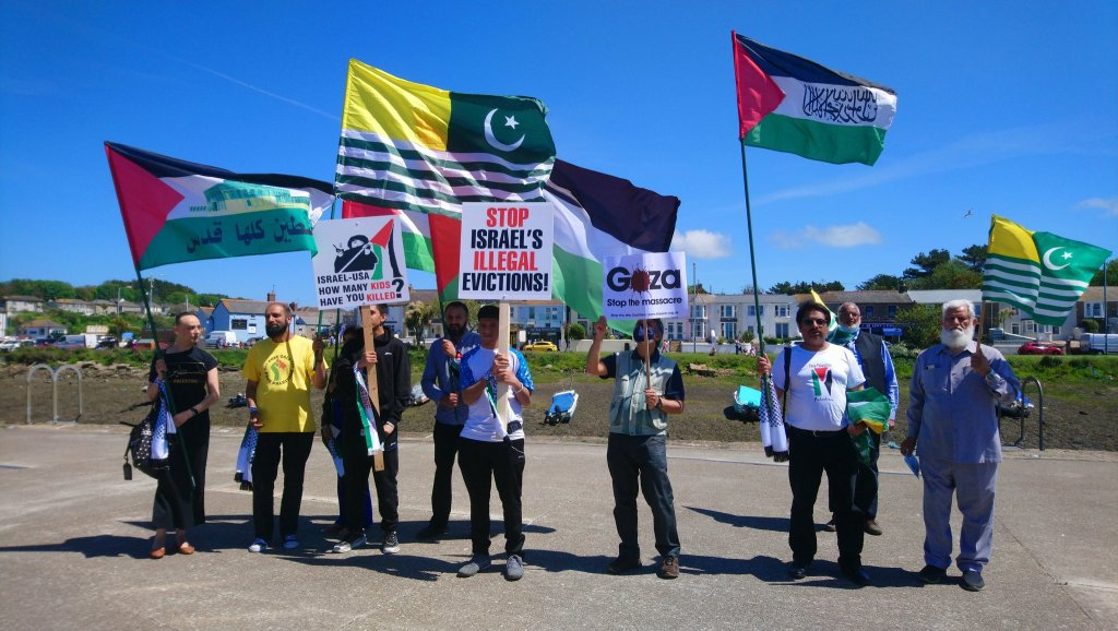 Protesters at the international day of resistance against G7 display national flags of liberation including Palestine