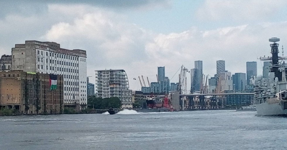 A boat on the dock outside DSEI passes in front of a disused building where a large Palestinian flag and an Extinction Rebellion banner have been dropped from the roof.