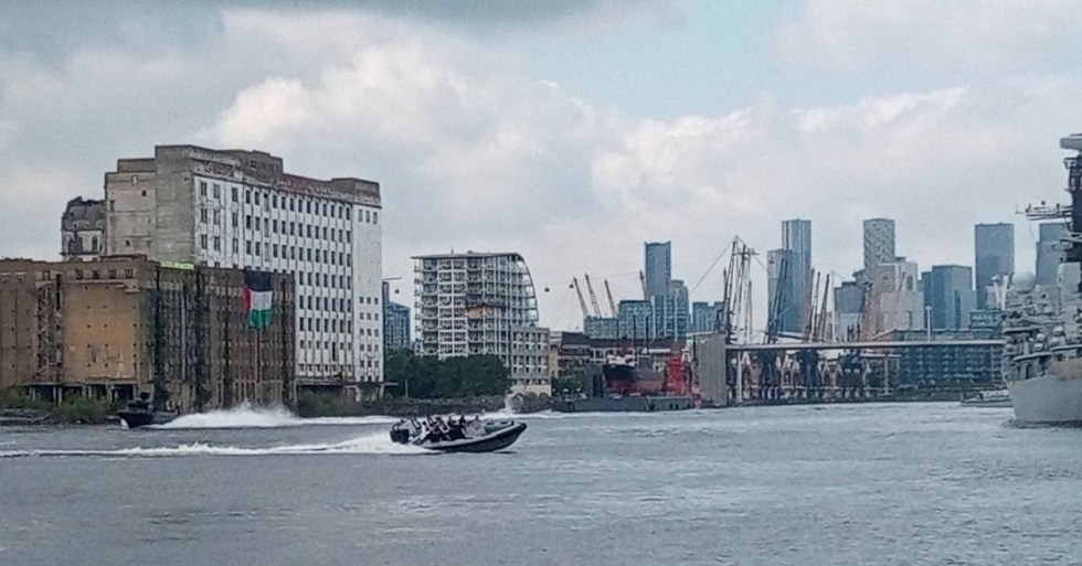 Boats on the dock outside DSEI passes in front of a disused building where a large Palestinian flag and an Extinction Rebellion banner have been dropped from the roof.