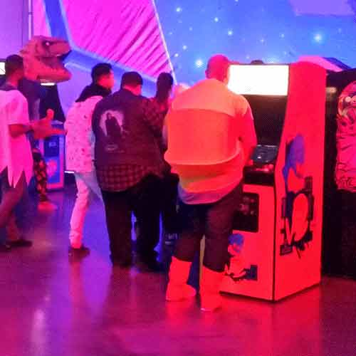 Company hosted Retro Party with Classic Arcades with costumed guest of Pacman playing a Pac Man Arcade Game