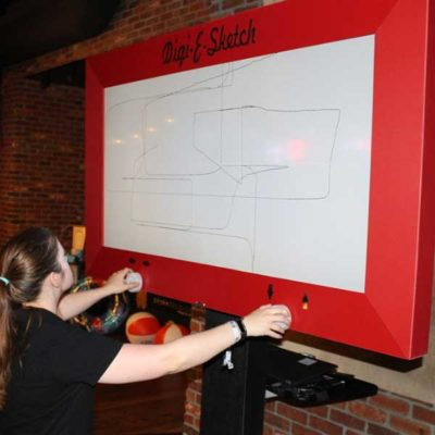 Girl playing Giant Etch A Sketch like Game at Event
